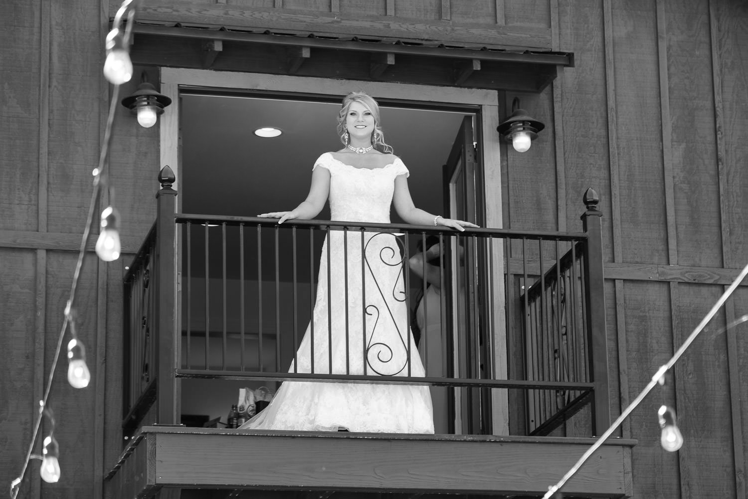 bride standing on a balcony at the barn at rock creek